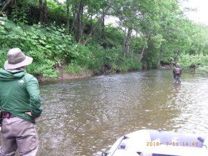 ゴムボートで川を下る杉坂さんとメンバー二人。